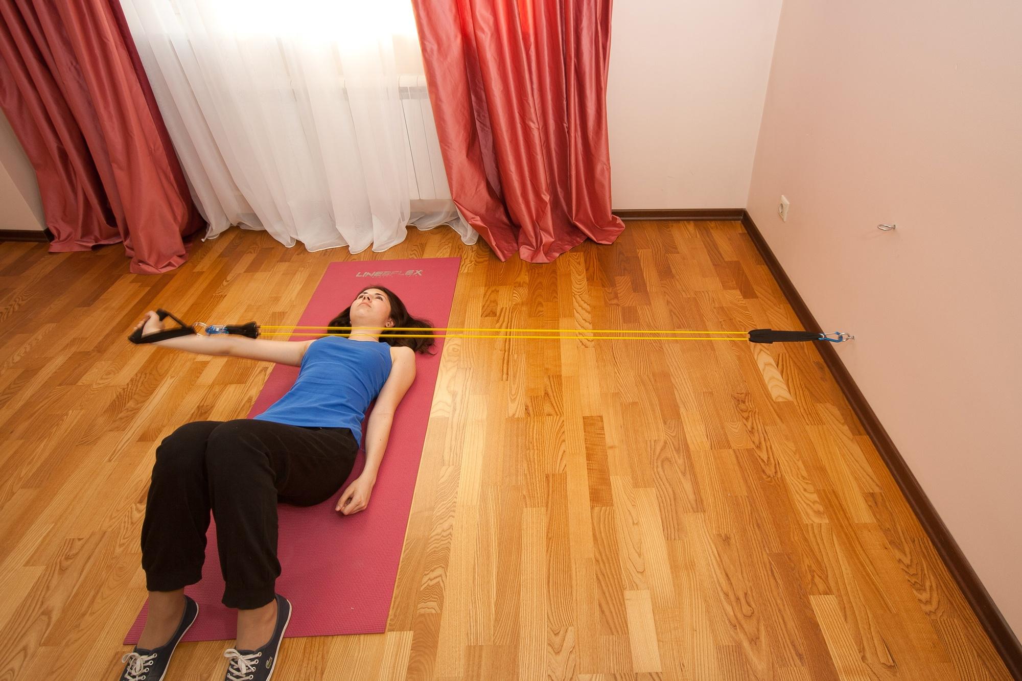 Упражнение с эспандером для мышц плеч и рук. Разведение одной руки лежа. Задние дельтовидные мышцы. Трапециевидные мышцы. Мышцы-вращатели плеча.